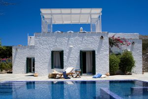 Exterior of Yria luxury sea view villa rental in Paros, with private pool, sunbed, trees & shutters