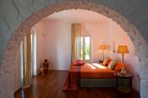 Archway to Yria Paros private pool villa elegant bedroom with king size bed, tables & lamps.