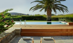 Sunbeds face the Yria Paros Boutique Hotel resort & Spa pool surrounded by wooden decking