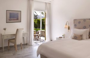 Bedroom area of Superior Double Room at Yria Hotel in Paros. Bed, chair, lamp & table by patio doors
