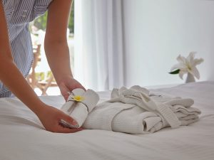 Maid places towels & robe on king size bed in luxury Executive Suite at Yria Boutique Hotel in Paros