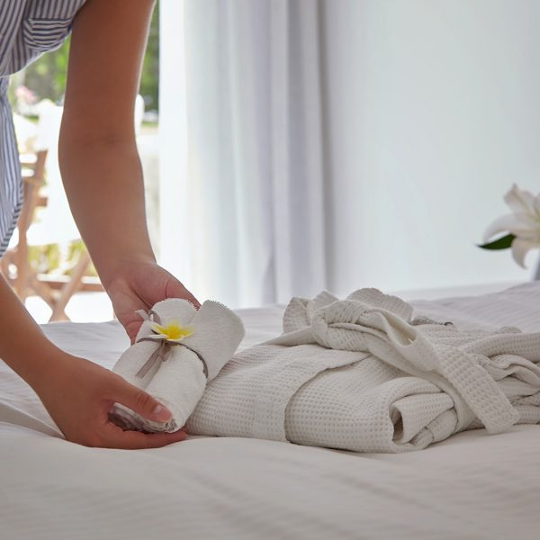 Maid places a towel on the bed in the Yria Island luxury Hotel & Spa Junior Suite in Paros
