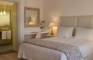 Executive Suite bedroom with bed, table, lamp & desk & open door to bathroom at Yria Hotel in Paros