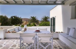 A guest enjoys the surrounding terrace with mountain & sea views in Yria Residence Suite in Paros