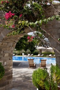 Archway in Yria Luxury Hotel & Spa resort gardens leading to pool area with sunbeds in Paros