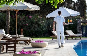 Bar waiter at Yria Island Boutique Hotel & Spa in Paros delivers tray of cocktails to the poolside